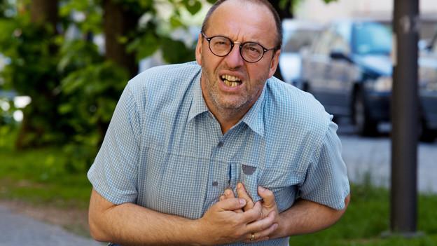 Mann mit schmerzverzertem Gesicht umklammert mit beiden Armen seine Brust.