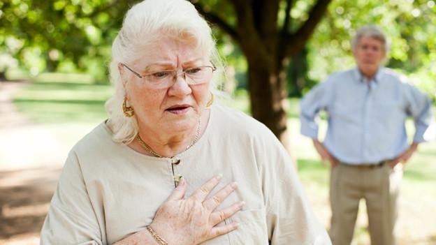Eine Frau mit schmerzverzerrtem Gesicht hält sich die rechte Hand auf die linke Brust.