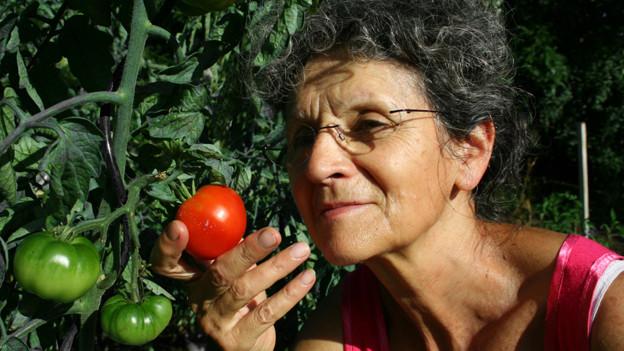 Eine Frau riecht an einer saftig roten Tomate.