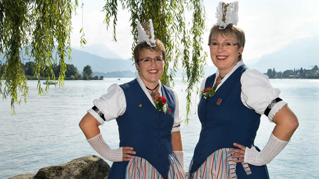 Die beiden Jodlerinnen stehen in ihren festlichen Trachten am Ufer eines Sees.