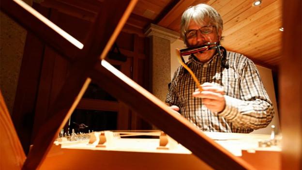 Der Sagenerzähler in Aktion, in einem schummrig beleuchteten Raum spielt er während der Erzählung zwischendurch Mundharmonika.