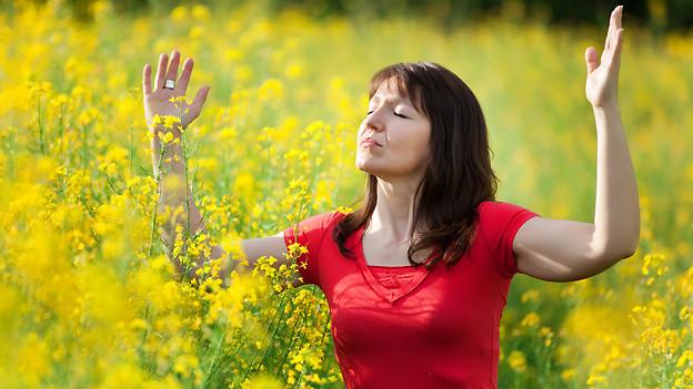 Eine Frau steht mit ausgebreiteten Armen mitten in einem Feld voller gelber Blumen.