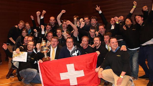 Die Musiker der Brass Band posieren mit Schweizer Fahne und Pokal als Wettbewerbssieger.