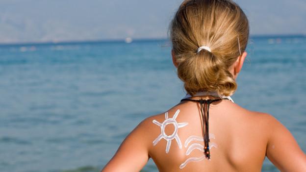 Ein Mädchen am Strand mit Blick aufs Meer. Auf dem Rücken eine mit Sonnencrème aufgetragene Sonne und Wellen.