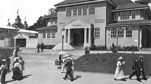 Historische Fotografie mit Ausstellungs-Besuchern, die vor dem Pavillon vorbei spazieren.