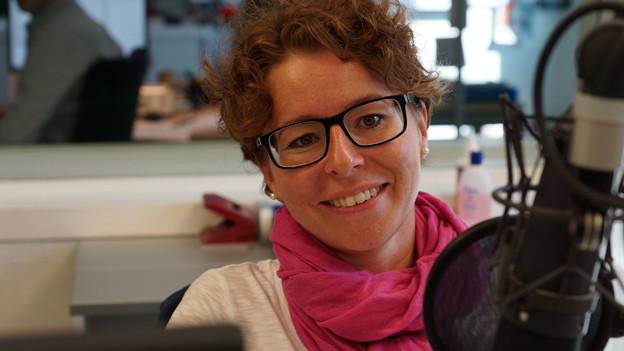 Nadja Räss mit rötlichem Lockenschopf vor dem Mikrofon im Sendestudio.