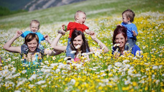 Drei Mütter mit ihren Kleinkindern auf den Schultern springen über Blumenwiese.