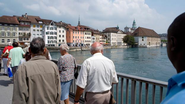 Fussgänger überqueren auf der Wengibrücke in Solothurn die Aare. Rechts im Hintergrund ist das Landhaus zu sehen.