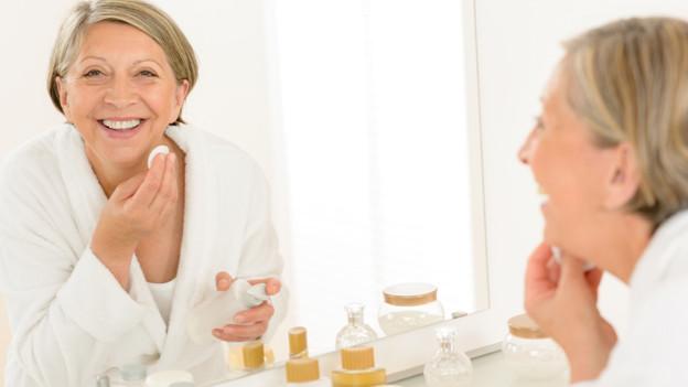 Eine Frau, die während der Hautpflege ihrem Spiegelbild entgegen lacht.