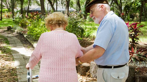 Ein älteres Paar auf einem Spaziergang in einer Allee.