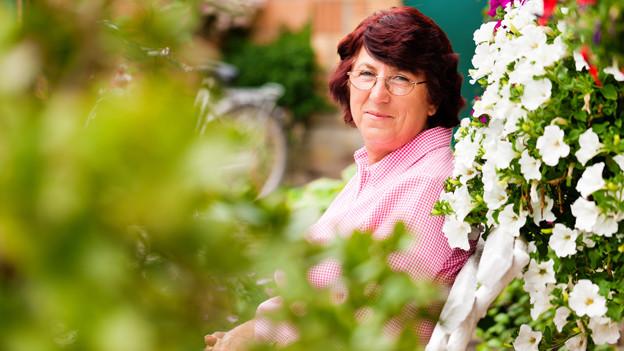 Eine Frau mit braunen Haaren sitzt zufrieden hinter einem blühenden Strauch weisser Petunien.