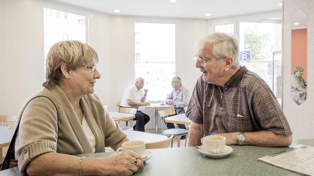 Zwei ältere Leute unterhalten sich sitzend an einer Theke.