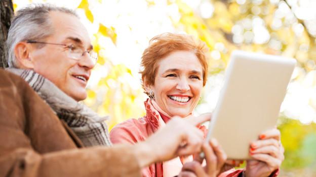 Ein Ehepaar sitzt auf einer Bank und surft auf einem Tablet im Internet.