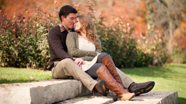 Ein junges Paar umarmt sich sitzend auf einer Treppe.