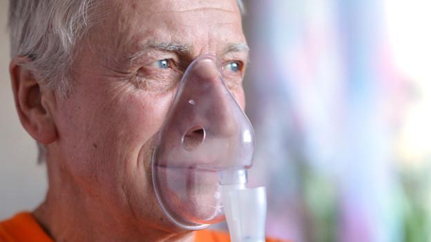 Ein Mann mit einer Maske zum Inhalhieren auf Nase und Mund.