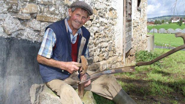 Der Bauer sitzt drausse von seiner Hütte auf einem Stein.