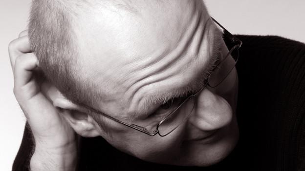 Schwarz-Weiss Fotografie eines Mannes mit Brille, der sich am Hinterkopf kratzt.