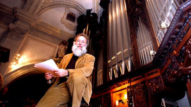 Der Organist steht vor den mächtigen Pfeifen der Kirchenorgel.