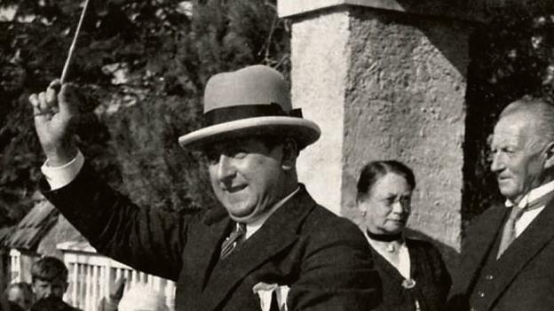 Mantegazzi im Zürich der 40-er oder 50-er Jahre, draussen auf der Strasse. Er schwingt den Dirigentenstab. Hinter ihm lauscht Publikum.