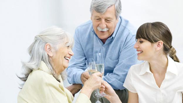 Rentnerpaar und junge Frau stossen an mit einem Glas Sekt.
