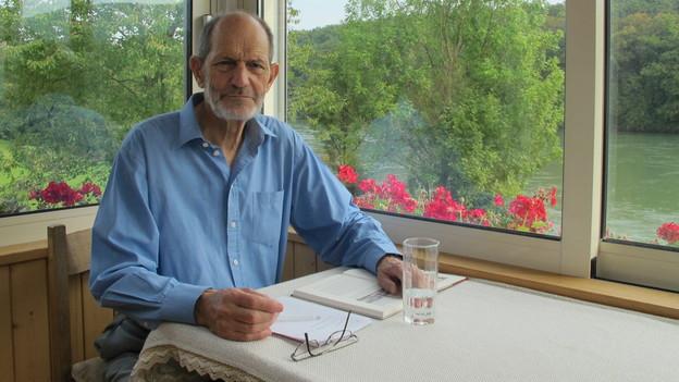 Max Baumann sitzt am Tisch vor einem Eckfenster mit Blick auf den Fluss.