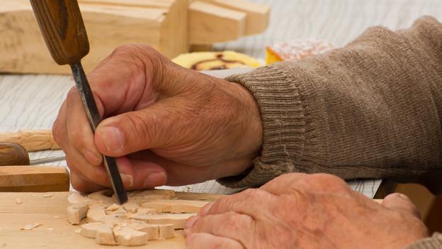 Hände, die mit einem Meissel ein Stück Holz schnitzen.