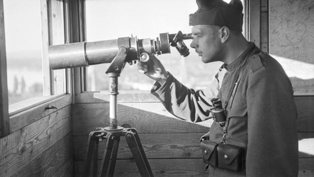 Mann in Schweizer Soldatenuniform der Vierziger-Jahre in einem hözernen Ausguck. Er blickt durch sein Fernrohr.