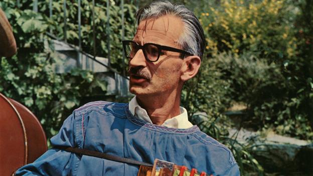 Der grauhaarige Musiker mit Brille spielt im Freien Schwyzerörgeli.