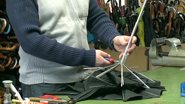 Baumann repariert einen kleinen, schwarzen Schirm auf seiner Werkstattbank.