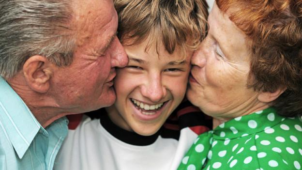 Ein Bub erhält von seinem Grossvater links und seiner Grossmutter rechts einen dicken Kuss auf die Wange gedrückt.