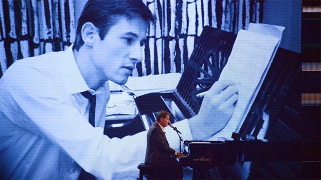 Udo Jürgens im Frack an Flügel sitzend. Im Hintergrund sieht man ihn auf einer Leinwand als junger Komponist, der ebenfalls am Flügel sitzt und Noten zu Papier bringt.