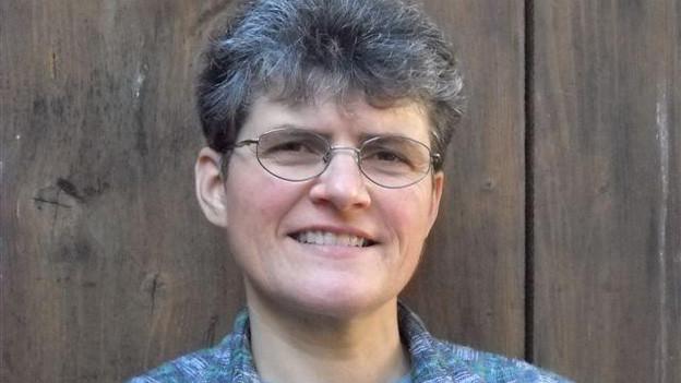 Porträt von Therese Leutwyler mit Kurzhaarschnitt und Brille.