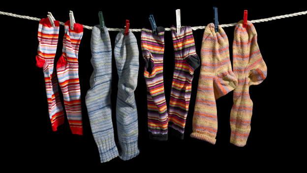 Vier Paar farbige Socken, aufgehängt an einer Wäscheleine.