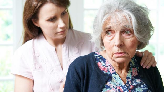 Traurige Seniorin. Ihre Enkelin oder Tochter legt ihre Hand beruhigend auf die Schulter.