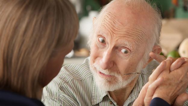 Ein alter Mann hält die Hand einer jüngeren Frau, die ihm eine Brille hinstreckt.