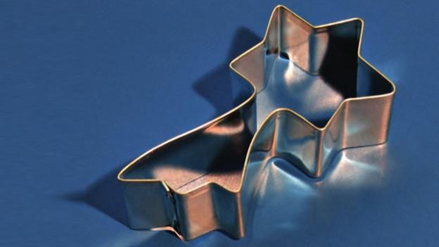 Eine sternförmige Ausstechform auf blauem Hintergrund.