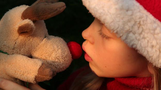 Ein Rentier aus Plüsch stupst mit seiner roten Nase die Nase eines Mädchens, das eine Weihnachtsmannmütze trägt.