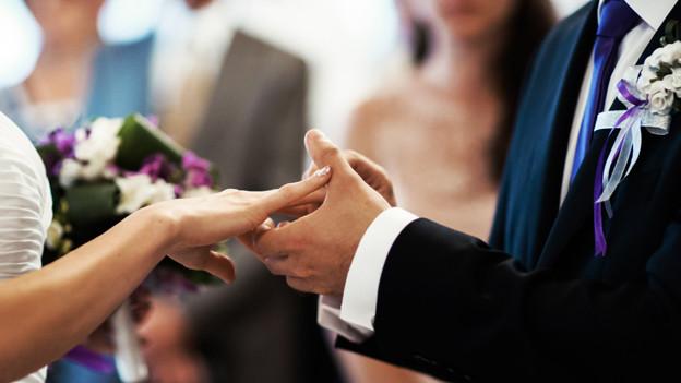 Ein Ehemann steckt seiner frisch Angetrauten den Ring an den Finger.
