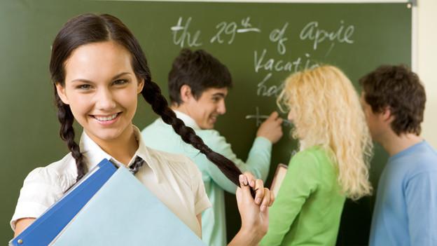 Zwei Schülerinnen und zwei Schüler im Klassenzimmer vor der Wandtafel.