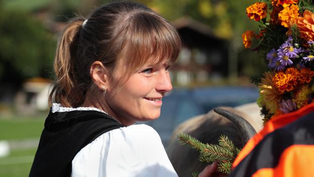 Eine junge Frau in ihrer Tracht bei einem Alpabzug.