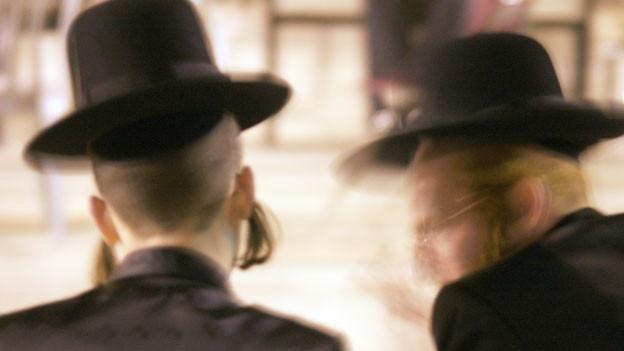 Zwei Orthodoxe Juden von hinten fotografiert.