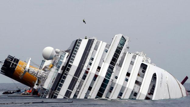 Costa Concordia liegt seitlich eingesunken im Meer.