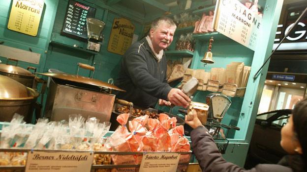 Marktverkäufer überreicht Kundin eine Tüte Magenbrot.