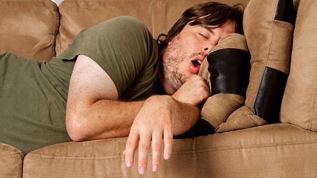 Ein Mann, der mit offenem Mund auf dem Sofa schläft.