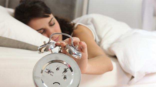 Eine Frau, die im Halbschlaf auf den Wecker haut.