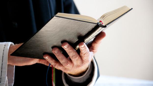 Pfarrer, der aus der Bibel liest.
