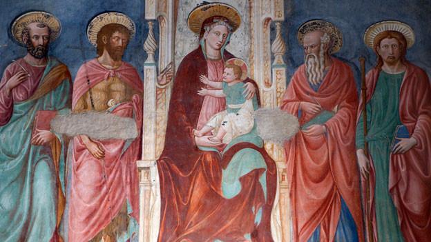 Bildnis von Maria mit Jesuskind auf Arm inmitten von Heiligen. Wandmalerei in katholischer Kirche.