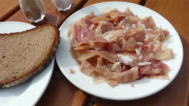 Ein Teller mit Ochsenmaulsalat, daneben eine Scheibe Brot.