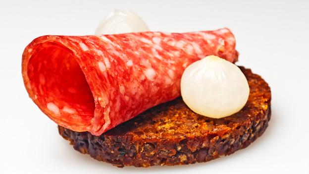 Eine Scheibe Pumpernickel, mit Salami und Silberzwiebeln belegt.