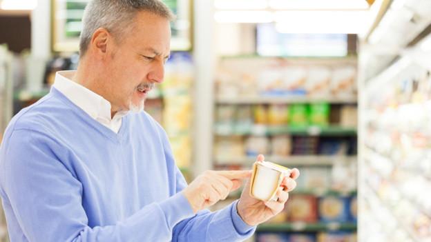 Ein Mann im Lebensmittelgeschäft mit einem Becher Joghurt in der Hand.